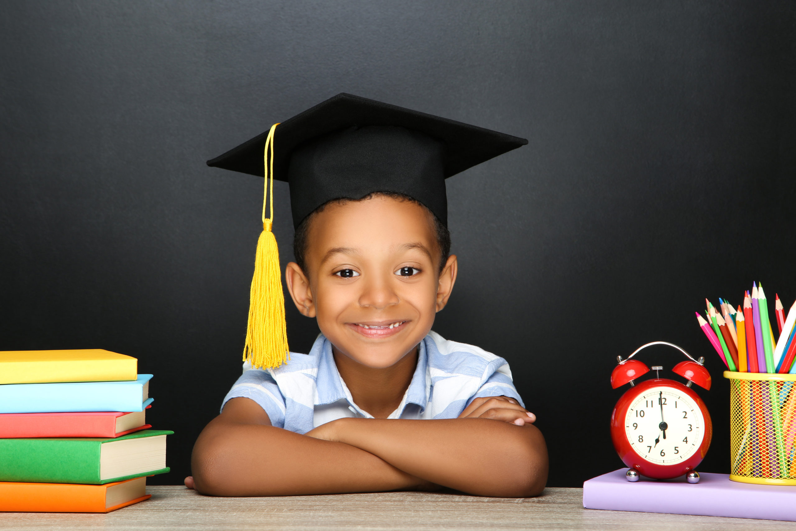 Young African American school boy sitting at desk with books, pencils and alarm clock on black background